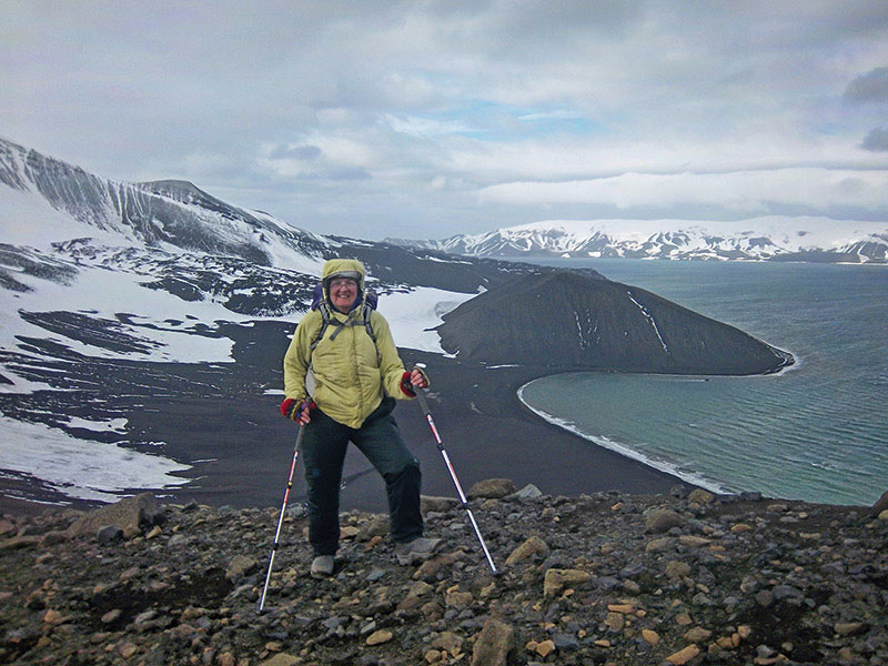 "Jody Bourgeois of the University of Washington, at Deception Island (an ocean-filled volcanic crater and a smaller cinder cone are in background) in Antarctica – during the ""Shackleton Slog,"" Bourgeois, a Shackleton history buff, led the glissade charge downhill to Stromness. Photo courtesy of Jody Bourgeois"