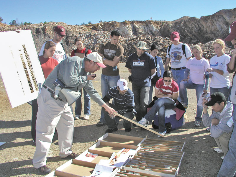 Roger Slatt shows his reservoir characterization class core that was taken from the outcrop in the background. A FMITM log from the same well is alongside the core. Photo courtesy of Roger Slatt