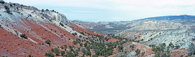 Utah complexity: The intensely folded Arapien Shale forms the core of the Sanpete- Sevier Valley antiform that trends essentially north-south. The location of theWolverine Federal Arapien Valley 24-1 well is along an east tributary of the drainage that is about the center of the photograph, less than two miles away. Photograph by Doug Sprinkel.