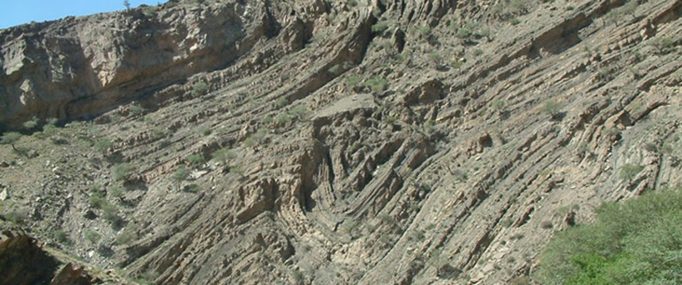 A fold in geology is when one or a stack of originally flat and planar surfaces, such as sedimentary strata, are bent or curved as a result of deformation by pressures from faults and other forces of nature.